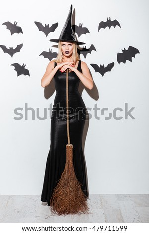 Attractive young woman in witch costume with hat standing and holding broom over white background