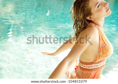 Attractive young woman inside a swimming pool in a tropical garden, wearing a pink dress and tilting her head back. - stock photo