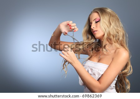 Attractive young woman is cutting her own hair. Studio shot over grey background. - stock photo