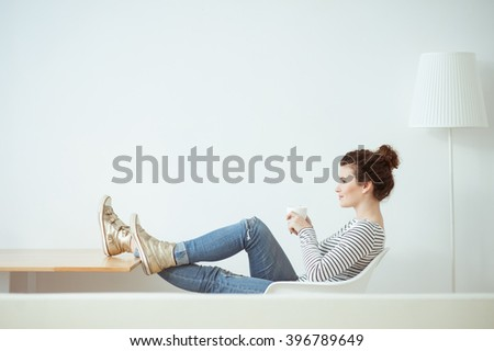 Attractive young woman is drinking hot beverage - stock photo
