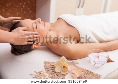 Attractive young woman is getting head massage at spa. She is lying and relaxing. The girl is smiling with closed eyes. The masseuse is standing and massaging female body carefully - stock photo