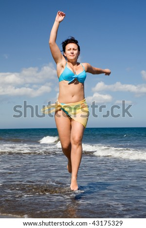 Attractive young woman is jumping on seashore - stock photo