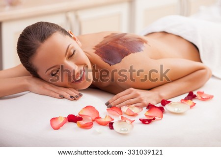 Attractive young woman is lying and smiling at spa. She is getting chocolate massage. The brown substance is on her naked back - stock photo