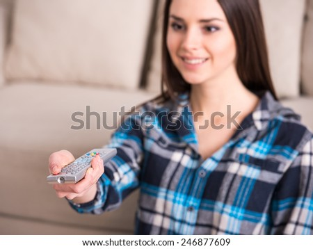 Attractive young woman is sitting down at home living room, using a control remote while watching tv. - stock photo