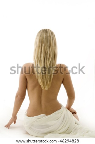 Attractive young woman is sitting in a sensual pose with bare back - stock photo
