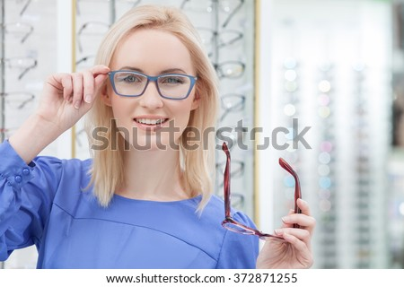 Attractive young woman is wearing spectacles in shop - stock photo