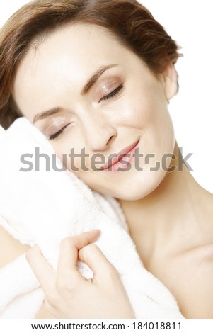 Attractive young woman isolated on white background wearing a bath towel.