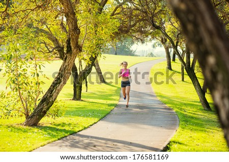 Attractive young woman jogging on Park Trail in the Early Morning.  Healthy Lifestyle Fitness Running Concept - stock photo
