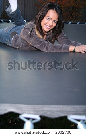 Attractive Young Woman Jumping on Trampoline and Having Fun in the Fall