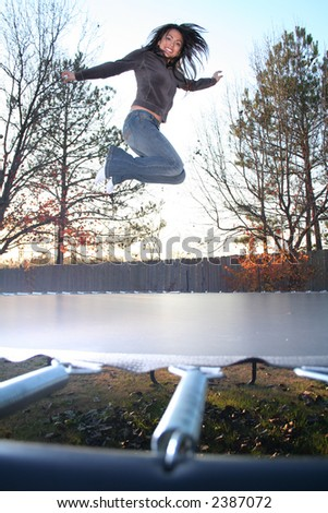 Attractive Young Woman Jumping on Trampoline and Having Fun in the Fall - stock photo