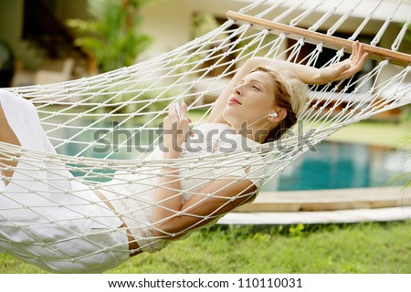 Attractive young woman laying down and relaxing on a white hammock while on vacation in a tropical garden, listening to music with her headphones. - stock photo