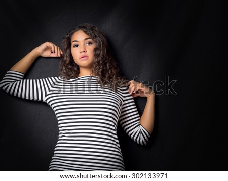 Attractive Young Woman Leaning Against Wall - stock photo