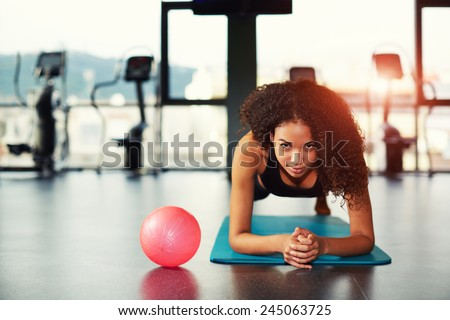 Attractive young woman leaning on her elbows doing exercise for buttocks muscles at gym - stock photo