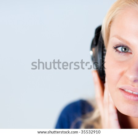 Attractive young woman listening music with headphones and looking at the camera