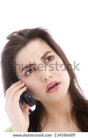 Attractive young woman listening to a call on a mobile phone looking up in consternation as she concentrates on what is being said - stock photo