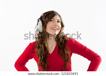 Attractive young woman listening to music with her headphones, isolated against a white background. - stock photo
