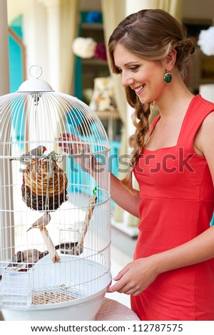 attractive young woman looking at birds in white cage and smiling - stock photo