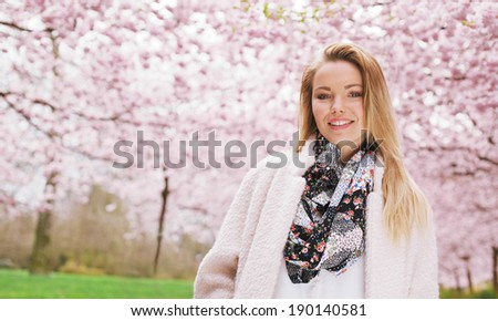 Attractive young woman looking at camera smiling while standing outdoors at spring park. Beautiful young lady wearing warm coat and scarf posing at spring blossom garden with copy space - stock photo
