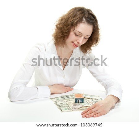 Attractive young woman looking at small house model and dollar banknotes dreaming of her own house - stock photo