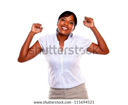 Attractive young woman looking at you and celebrating a victory on isolated background - stock photo
