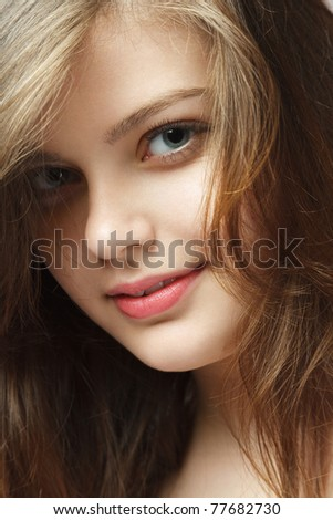 Attractive young woman looking to camera close-up studio portrait