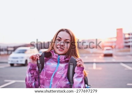 Attractive young woman looking to camera while adjusting her backpack. A bit tired but still ready to continue her trip. Freedom, tourism and backpacking concept. Urban scenery - stock photo