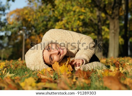 Attractive young woman lying against autumn leaves. Outdoor shot - stock photo