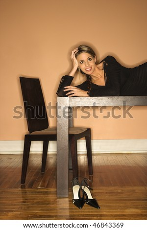 Attractive young woman lying on a table and smiling. She has placed her shoes on the floor. Vertical shot - stock photo