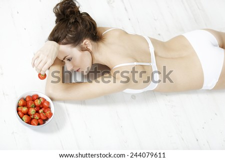 Attractive young woman lying on the floor in her underwear enjoying fresh strawberries - stock photo