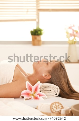 Attractive young woman lying with eyes closed on massage bed in spa.