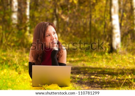 Attractive young woman lying with laptop on autumn background