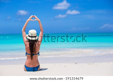 Attractive young woman making a heart with hands - stock photo