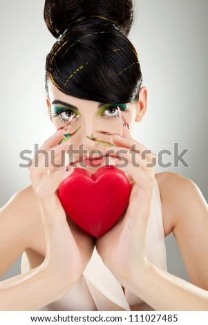 Attractive young woman model with excentric make-up and manicure holding a heart - stock photo