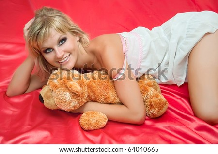 attractive young woman on a bed on pink with toy - stock photo