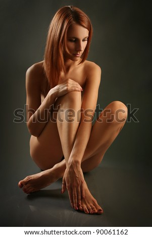 attractive young woman on dark background - stock photo