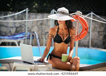 attractive young woman on poolside, browsing web on laptop with cup of coffee - stock photo