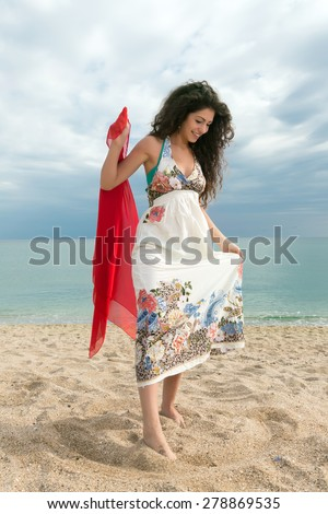 Attractive young woman on the beach with her feet in the sand - stock photo