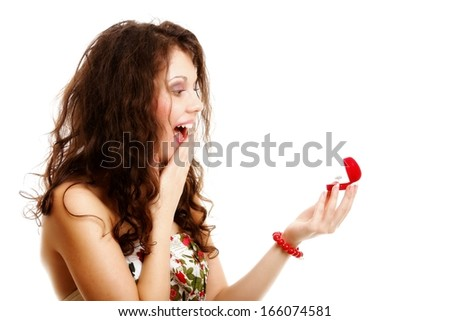 Attractive young woman opens a present heart shaped red box  and is surprised happy by an engagement ring