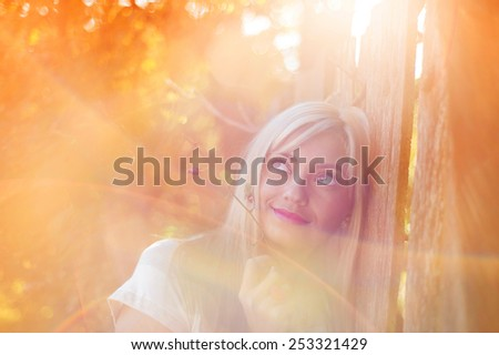 Attractive young woman outside next to the wooden fence.