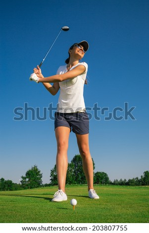 Attractive young woman playing golf - stock photo