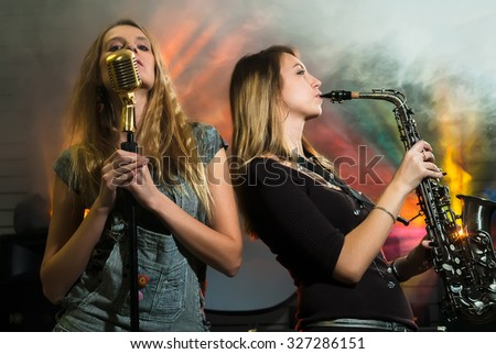 Attractive young woman plays on saxophone and other one sing s in microphone on concert - stock photo