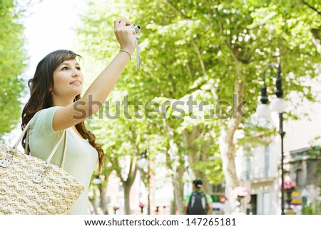 Attractive young woman pointing her digital photo camera up in a destination city to take a picture while traveling and doing tourism during a sunny day. - stock photo