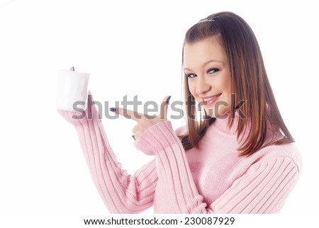 Attractive young woman points finger to coffee cup - stock photo
