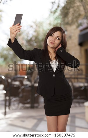 Attractive young woman poses in front of her cell phone.