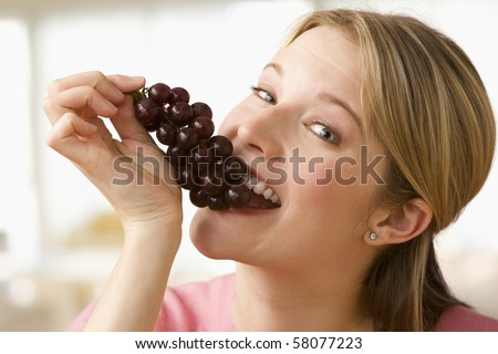Attractive young woman poses with a cluster of grapes partially in her mouth.  Horizontal shot.