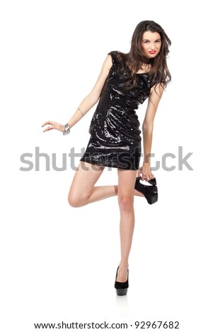 Attractive young woman posing in sequin dress, with alluring smile and looking at camera, playing with shoes. Studio image, isolated on white background.