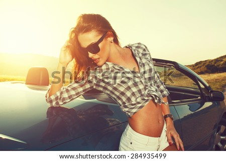 Attractive young woman posing leaning on convertible car at sunset - stock photo