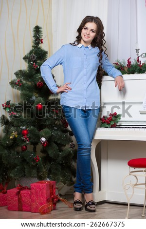 Attractive young woman posing near a fir-tree and white piano - stock photo