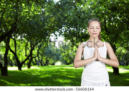 Attractive young woman practices yoga in the park - stock photo