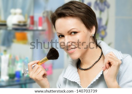 attractive young woman preening front of a mirror